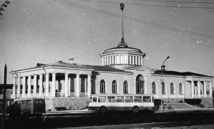 Советские автомобили на фоне здания железнодорожного вокзала в Павловске
